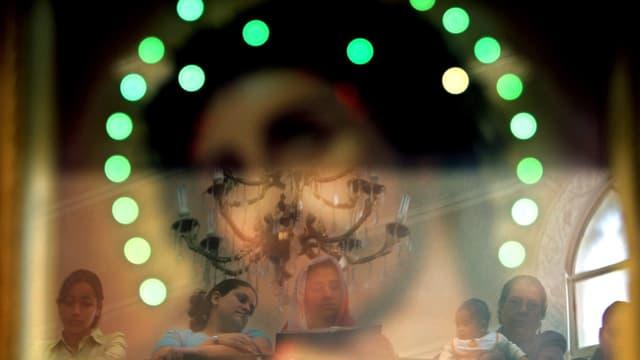 Kopten hinter einer sich reflektierenden Glasscheibe.