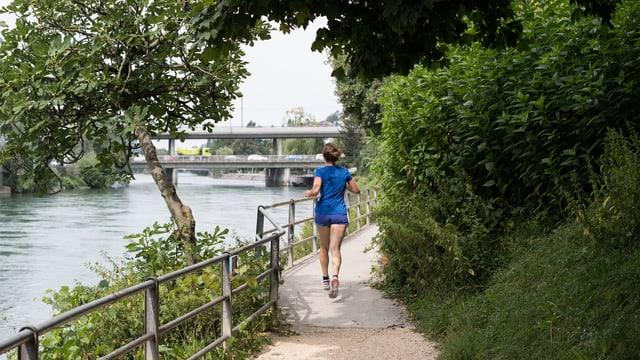 Eine Joggerin auf einem Laufweg entlang der Limmat.