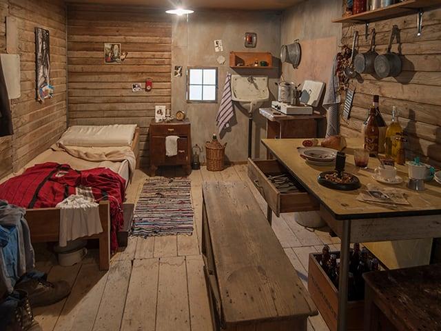 Blick in eine Holzbaracke mit einem Bett und einem Esstisch.