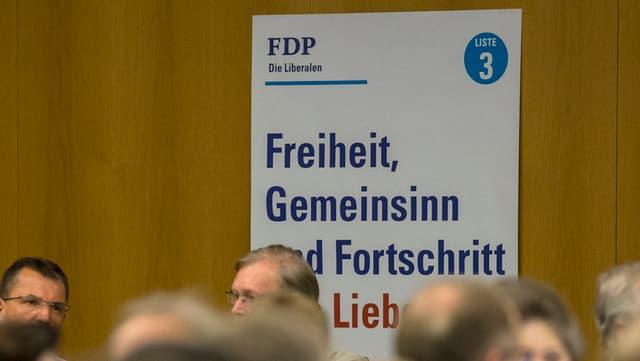 An einer Wand hängt ein Wahlplakat der FDP