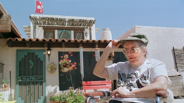 EKR im Rollstuhl vor ihrem Haus in Arizona mit dem Schweizerkreuz beflaggt.