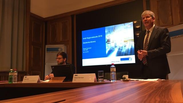 Medienkonferenz im Gebäude der Neuen Aargauer Bank in Aarau, im Hintergrund läuft eine Powerpoint-Präsentation.