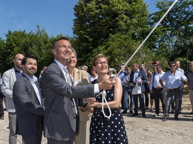 Jaques Boschung, Leiter Infrastruktur der SBB und Regierungsrätin Sabine Pegoraro rollen beim Spatenstich ein Plakat aus.