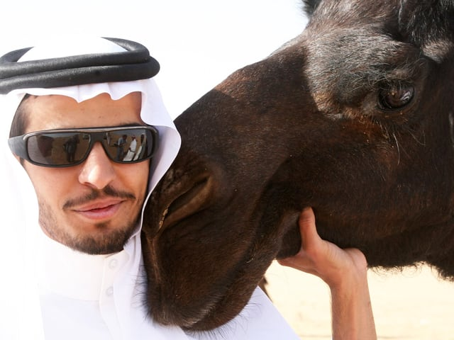 Mann schmiegt sich an den Kopf des Kamels.