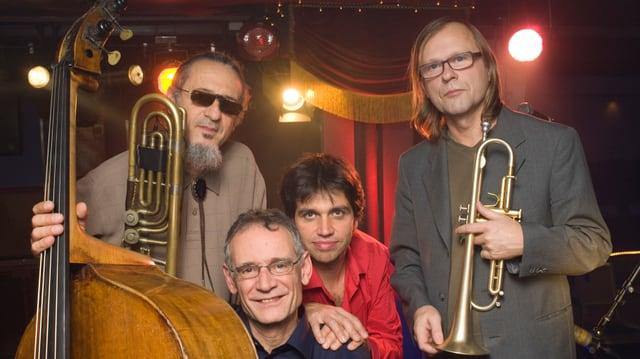 Vier Jazz-Musiker posieren auf einer Bühne.