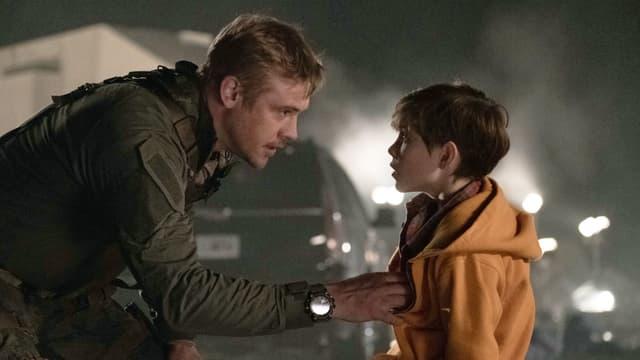 Ein Mann bpckt sich zu einem Jungen herunter. Er hält ihn an der Jacke und spricht mit ihm.