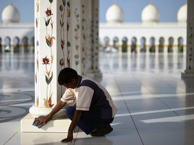 Ein Arbeitsmigrant putzt den Fuss einer Säule im Atrium einer Moschee.
