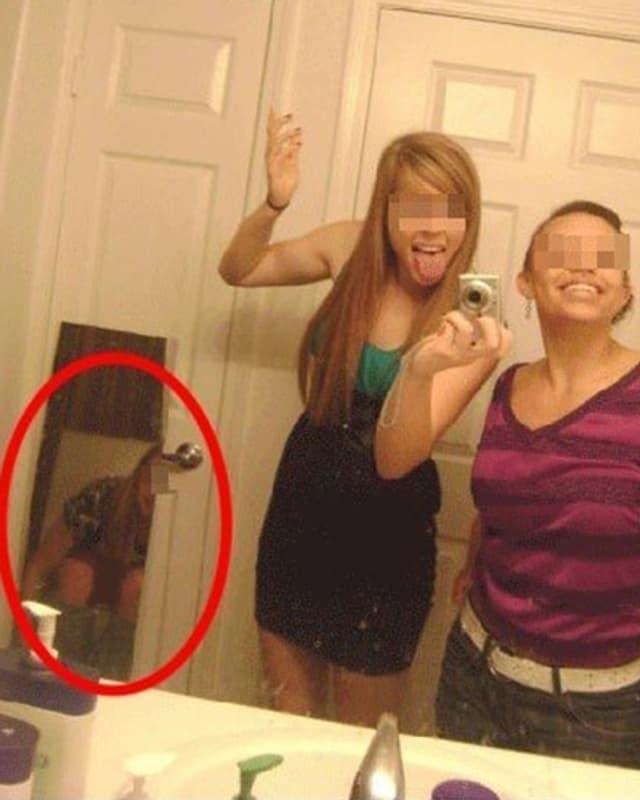 Ein Selfie, bei dem eine dritte Frau im Spiegel zu sehen ist – auf dem Klo.