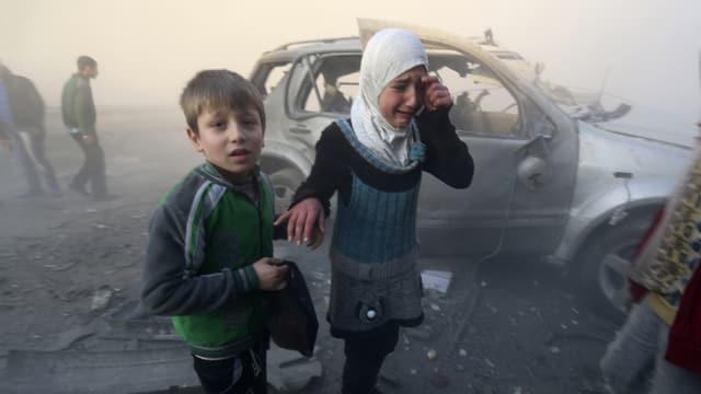 Ein Junge und ein Mädchen stehen schockiert im Staub nach einem Bombenabwurf, das Mädchen mit weissem Kopftuch weint.