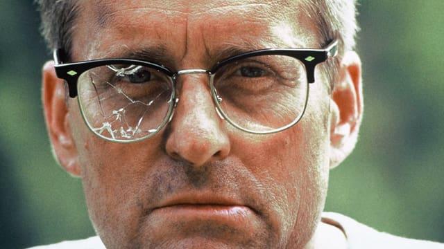 Ein Mann mit zerbrochener Brille sieht in die Kamera.