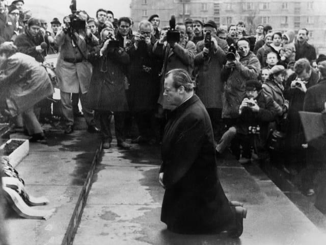 Willy Brandt kniet auf einer Treppe, neben ihm viele Presseleute