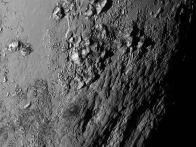 Aufnahme von Plutos Oberfläche nahe am Äquator mit Bergen und Schluchten.