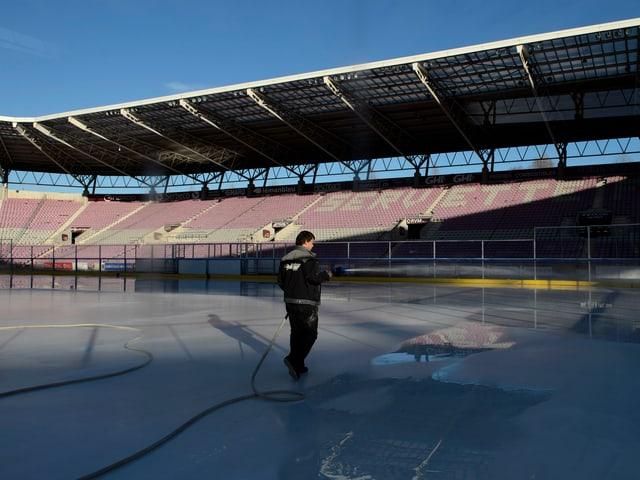 Ein Helfer bringt das Eis für das Freiluftspiel vom Samstag in Schuss.