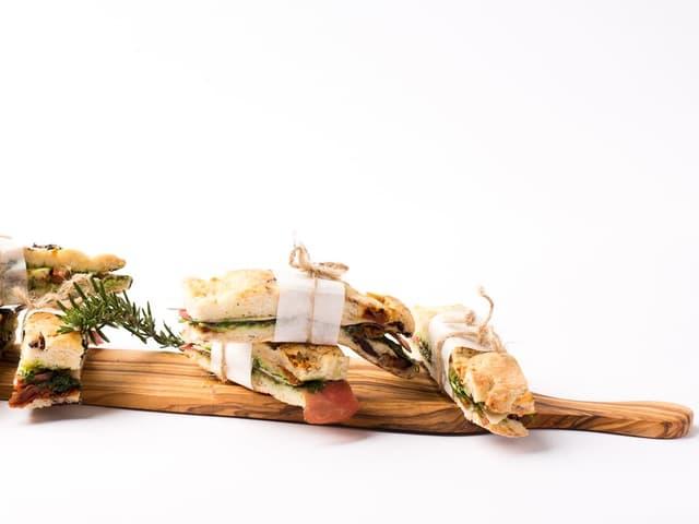 Sandwiches nebeneinander auf einem Holzbrett