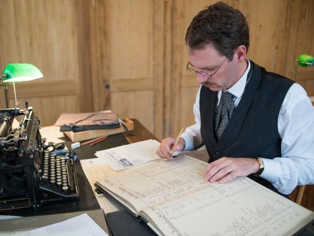 Buchhalter Thalmann im Fabrikbüro mit Buch, Schreibmaschine, Tinte und Feder auf Tisch