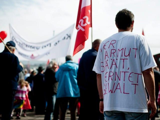 Ein Demonstrant trägt ein T-Shirt mit der Aufschrift «Wer Armut sät, erntet Gewalt»