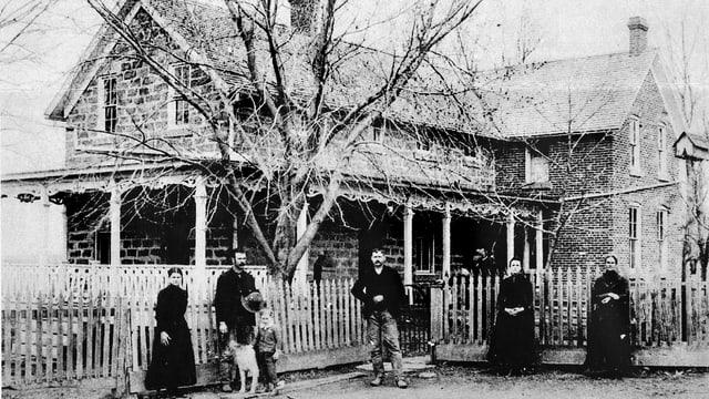 Schwarzweissfoto: Fünf Menschen und ein Hund stehen vor dem Gartenzaun eines Backstein-Hauses.