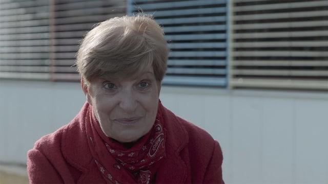 Frau in roten Mantel und kurzen Haaren schaut in die Kamera.