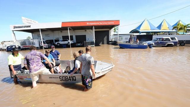 Menschen steigen in ein Boot, dahinter eine Tankstelle.