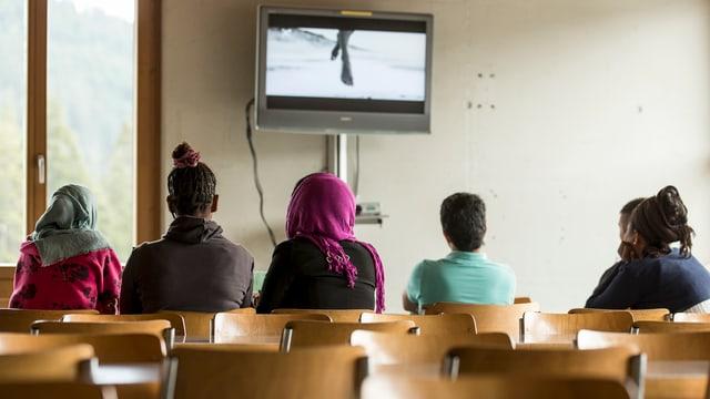 Mehrere Frauen und Mädchen schauen mit dem Rücken zur Kamera auf einen Bildschirn.