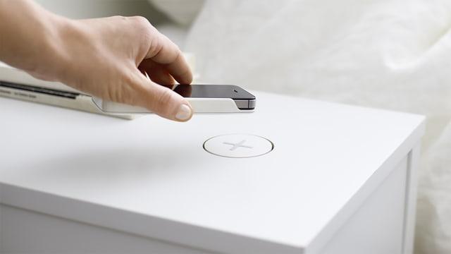 Ein weisser Nachttisch mit einer Markierung darauf, ein Plus-Zeichen, eine Hand, die das ein Smartphone an diese Markierung hält.