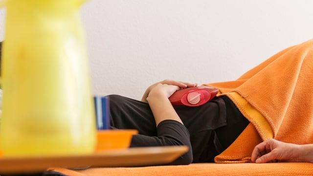 Eine Frau hält sich eine Wärmeflasche auf den Bauch.