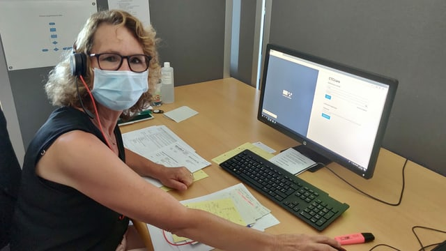 Eine Frau mit Mundschutz vor einem Computer.