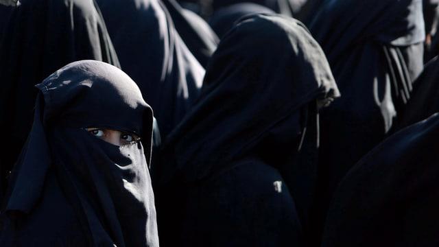 Frauen im Tschador, eine blickt zum Fotografen.
