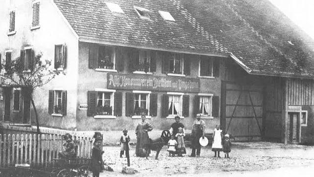Konsumverein Dietlikon: Mehrere Personen stehen vor einem Bauernhaus mit der Aufschrift Konsumverein.
