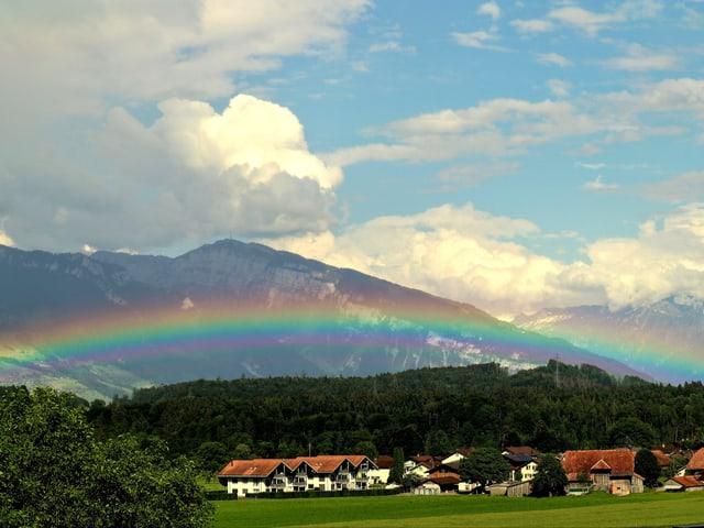 Flacher Regenbogen vor Bergkulisse.