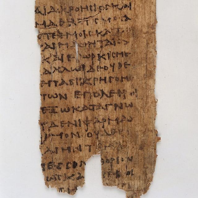 Ein zerfetztes Stück mit schwarzer, griechischer Schrift.