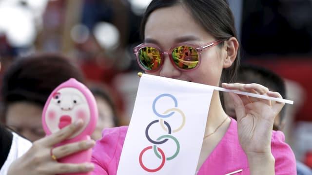 Eine Chinesin mit Sonnebrille und einem Wimpel mit Olympischen Ringen macht ein Selfie.