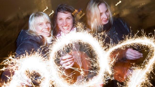 Drei Frauen feiern mit Feuerwerk das neue Jahr.