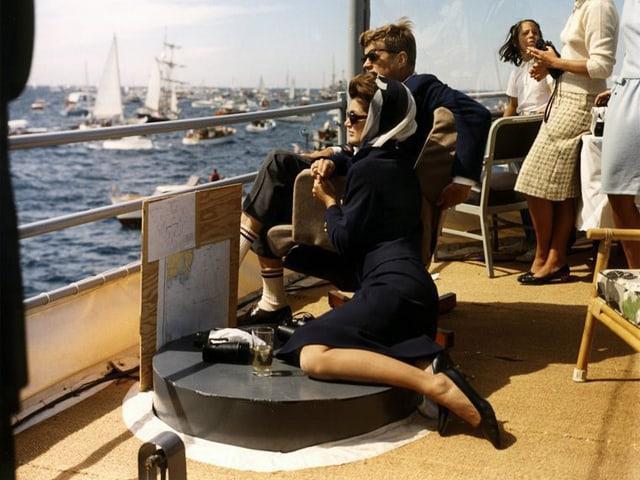 Ein Mann und eine Frau mit Sonnenbrille sitzen auf Deck eines Bootes und schauen einem Segelwettkampf zu.