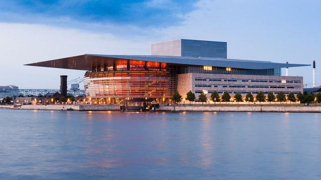 Blick auf ein modernes Gebäude, umgeben von Wasser. Die Königliche Oper auf der Insel Holmen von Kopenhagen ist die dänische Nationaloper und eine der modernsten Bühnen der Welt. Das Gebäude wurde von Henning Larsen entworfen.