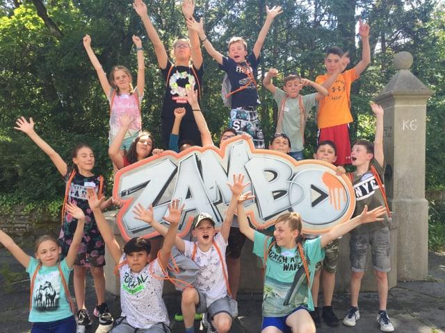 Schulklasse mit Zambo-Schild vor und auf dem Brunnen