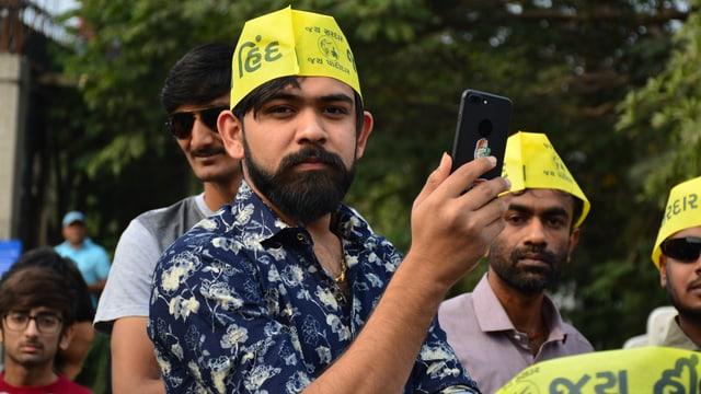 Ein junger Mann mit Handy und gelbem Käppi.