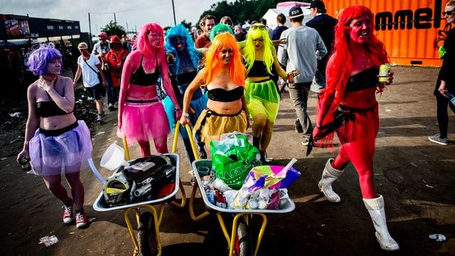Sechs Frauen in neonfarbigen Kleidern und Schubkarren