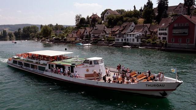 Ein Schiff mit Passagieren fährt an Stein am Rhein vorbei