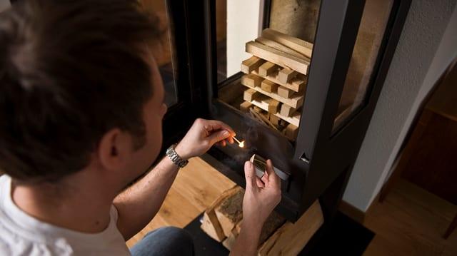 Mann zündet Holz im Schwedenofen an