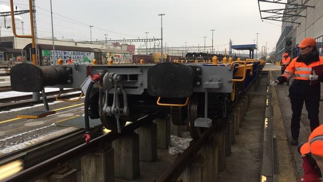 Rangierarbeiter neben einem unbeladenen Güterwagen.