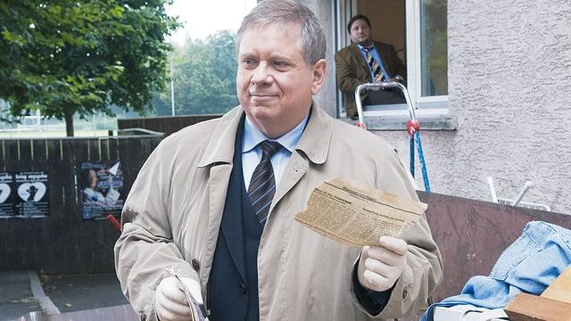 Mann hält Zettel in der Hand