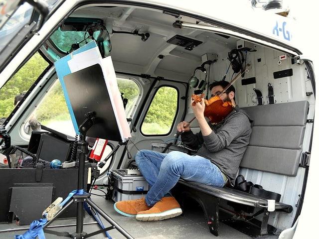 Ein Geiger sitzt in einem Helikopter und spielt Geige.