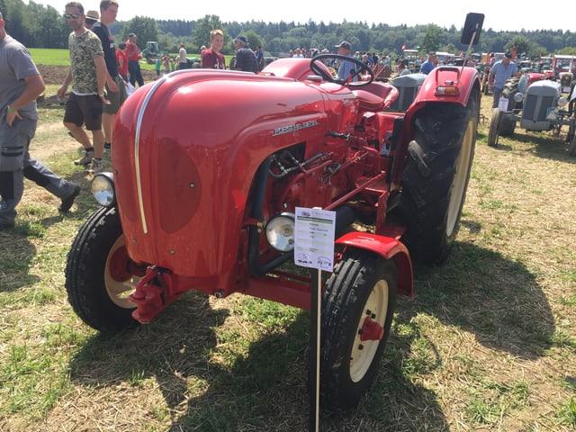 Ein roter Porsche-Traktor mit geschwungener Haube