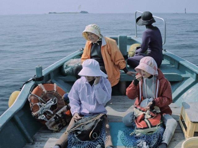 Vier Frauen sitzen auf einem Fischerboot.