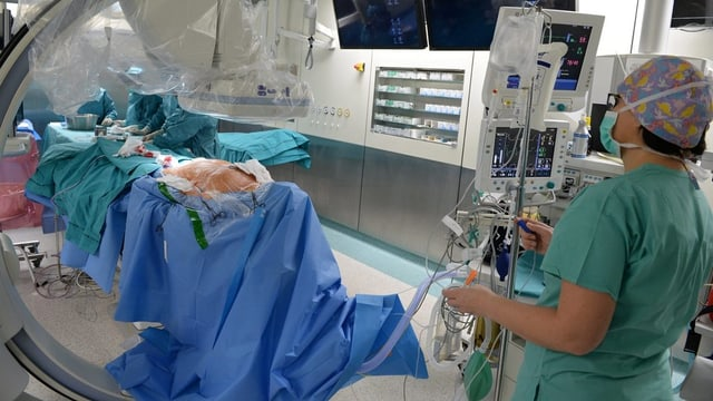 Operationssaal, man sieht eine Person, viele Geräte und einige blaue Tücher.