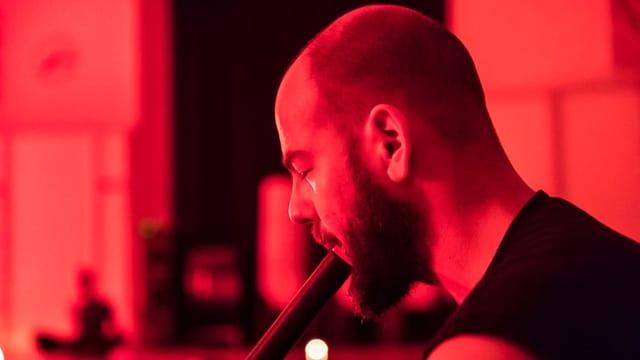 Mann mit geschlossenen Augen spielt ein nicht genau erkennbares Instrument.