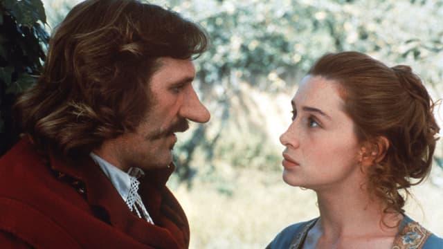 Ein Mann mit sehr grosser Nase schaut einer jungen Frau in die Augen.