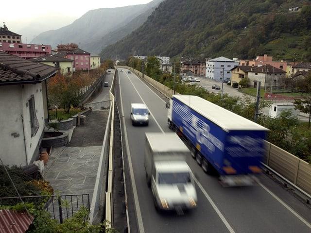 Lastwagen auf Autobahn inmitten von Häusern