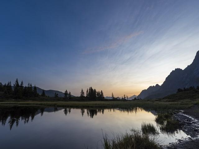 Pastellfarbener Himmel mit Berge und See.